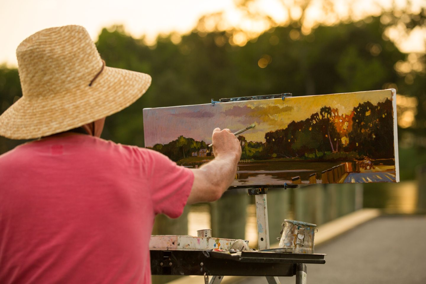Man painting outside during sunset
